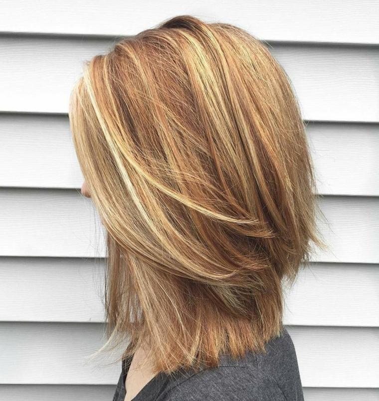 taglio di capelli scalati, una proposta di media lunghezza con ciuffo a lato e striature più chiare