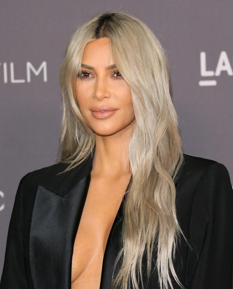 Capelli lunghi di colore biondo platino di Kim Kardashian, acconciatura con riga al centro e lunghezze mosse