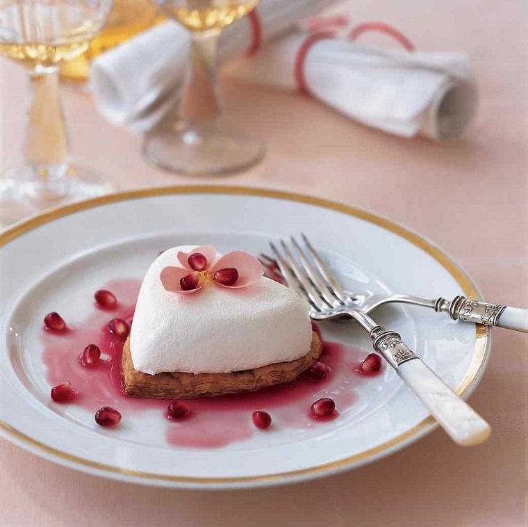 Torta a forma di cuore, cheesecake con decorazione di melograno e fiore rosa