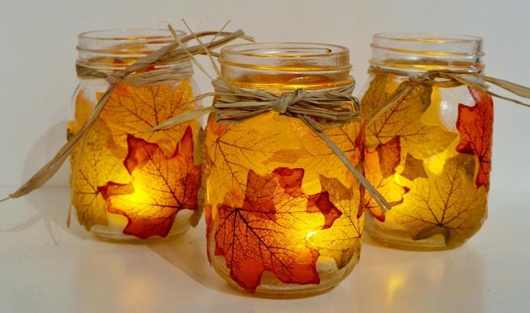 Idea per utilizzare i barattoli di vetro come portacandele, decorati con foglie secche a tema autunnale