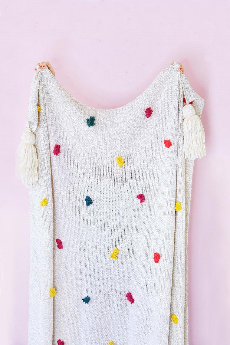 Come decorare la coperta di lana con dei fili di lana colorati in punti diversi