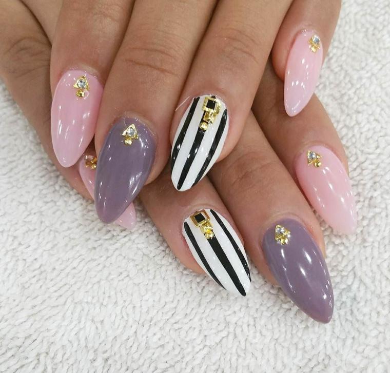 Unghie a stiletto di colore viola e rosa, accent nail bianco con linee nere e decorazioni con brillantini