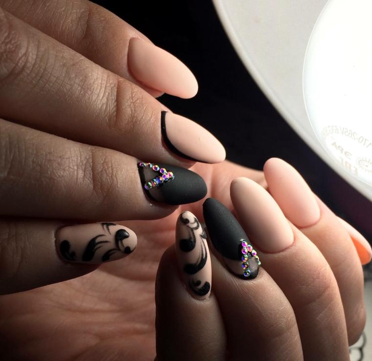 Smalto per unghie effetto mat di colore beige e nero, decorazioni con brillantini e disegni floreali