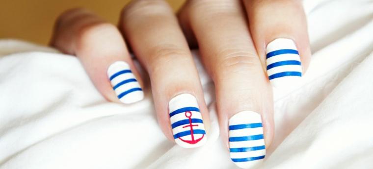 Unghie estive a tema navy, smalto base colore bianco con strisce blu e disegno ancora