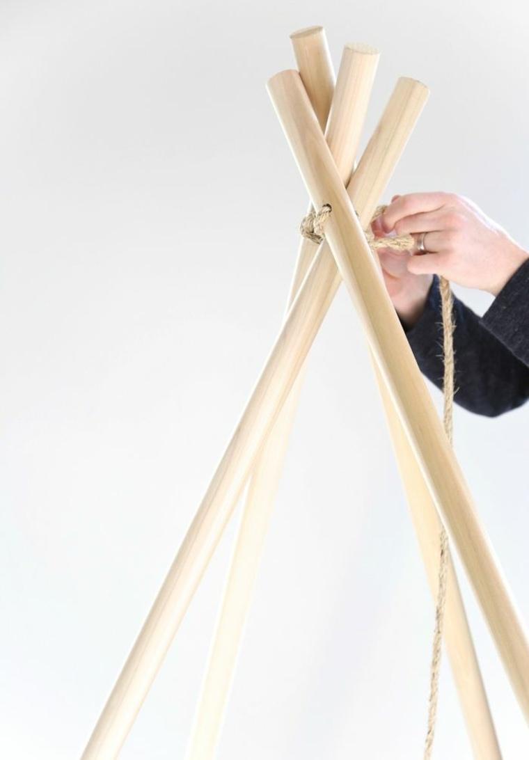 Costruzione con pezzi di legno di una tenda per bambini, posizione X e legare con della corda