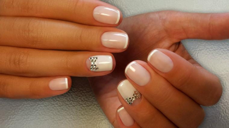 French manicure classica con decorazioni brillantini sul dito anulare