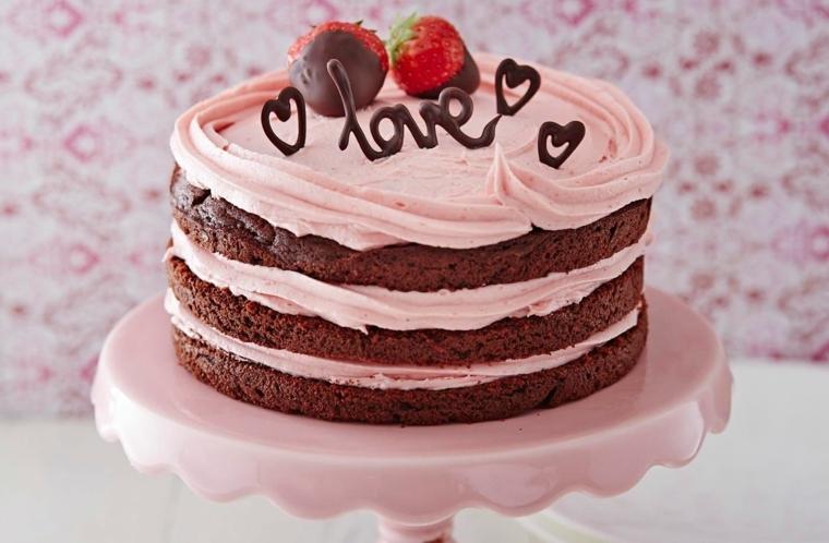 Torta al cioccolato con tre strati di crema di colore rosa, decorata con fragole e scritta Love