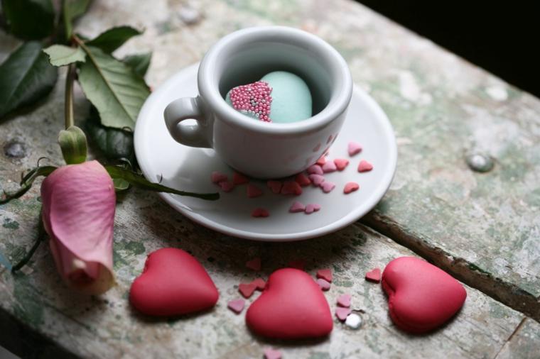 Biscotti macarons di colore rosa a forma di cuore, tazza di caffè con sorpresa dentro