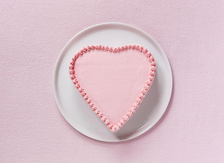 Una torta a fora di cuore con crema rosa e decorazioni laterali con panna montata