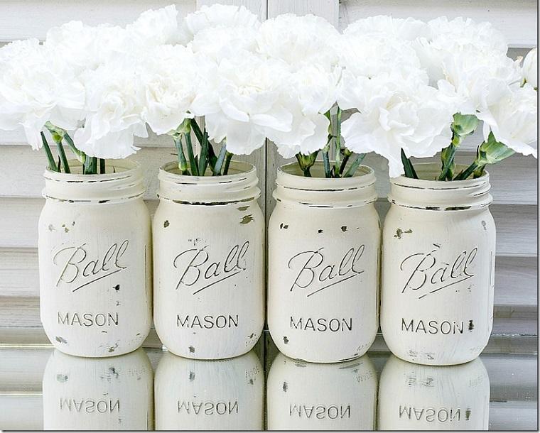 Fai da te casa e un'idea per riutilizzare i barattoli di vetro, dipinti di colore bianco e utilizzati come vasi