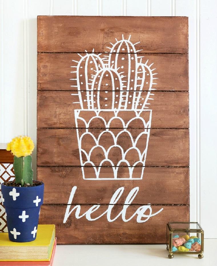 Riciclo creativo e un pannello decorativo in pallet con disegno colore bianco cactus e scritta Hello
