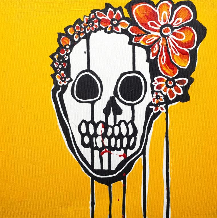 un quadro con un grande teschio in stile messicano con dei fiori intorno alla testa