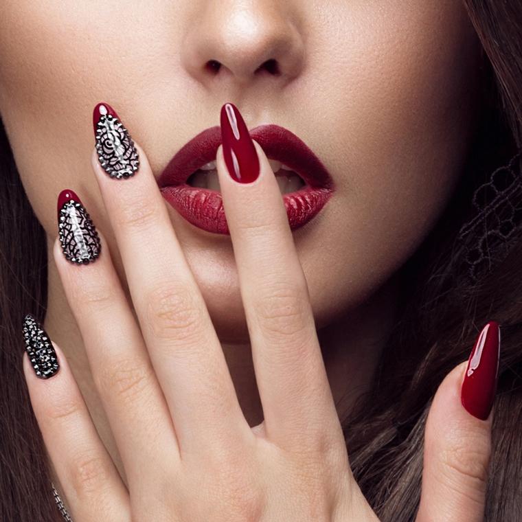 Manicure a stiletto con punta arrotondata, smalto rosso con decorazioni di colore argento
