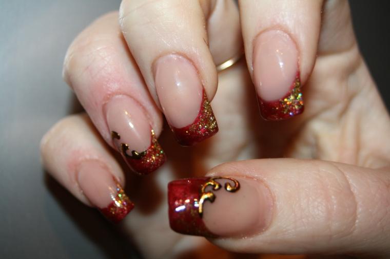 Unghie con french manicure particolare di colore rosso e glitter glossy in oro