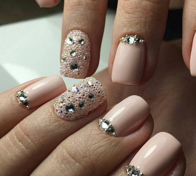 Unghie con smalto gel di colore rosa, decorazioni con brillantini e accent nail effetto sugar sul dito anulare