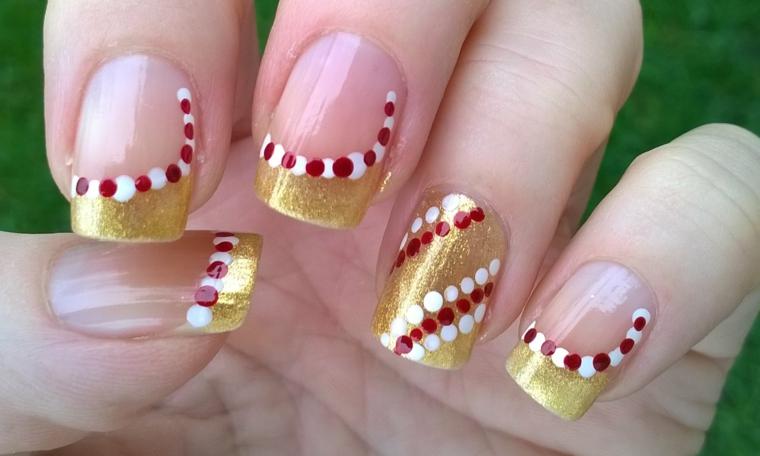 Unghie decorate per Natale, smalto colore giallo glitter, rosso e bianco su una base trasparente