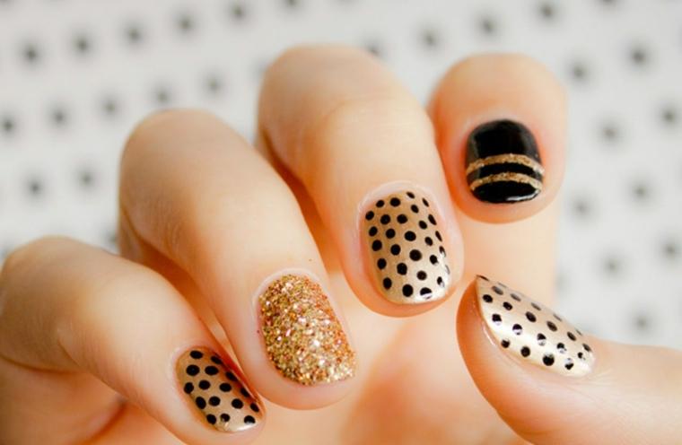 Unghie corte con uno smalto gel di colore beige e decorazioni con puntini neri e accent nail glossy
