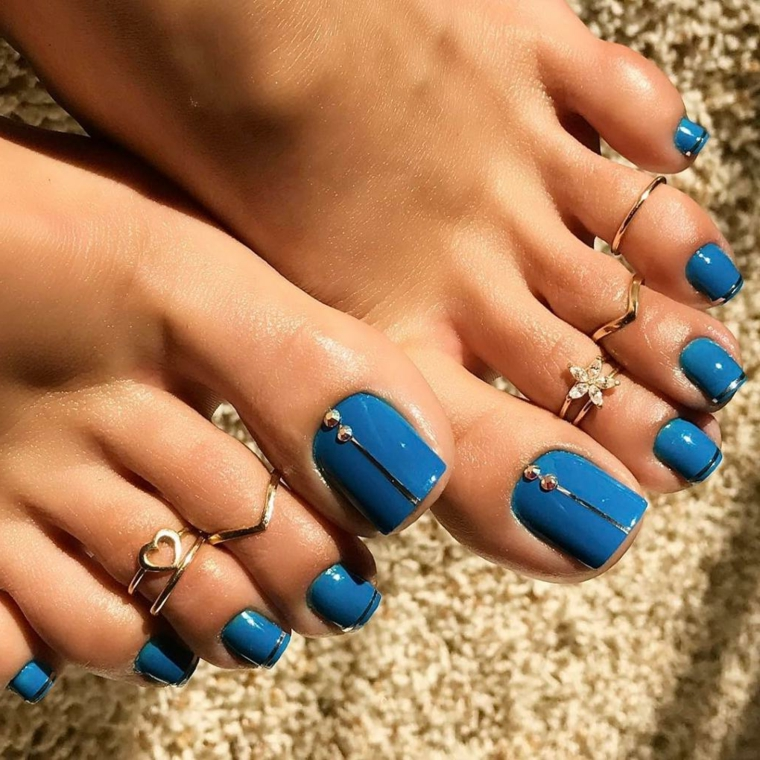 Unghie nail art sulle dita dei piedi, pedicure di colore blu e decorazioni con brillantini argento