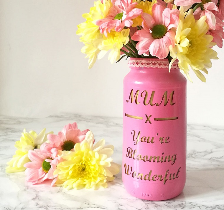 Fai da te casa e un'idea per riutilizzare e decorare il barattolo di vetro, dipinto di colore rosa con scritta e utilizzato come vaso