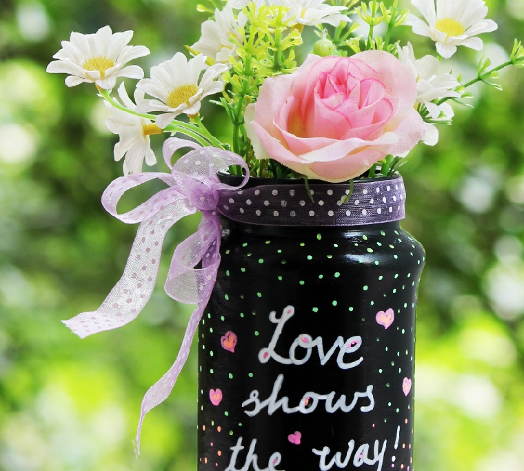 Arte del riciclo di un barattolo di vetro, dipinto di colore nero e decorato con un nastro, da utilizzare come vaso