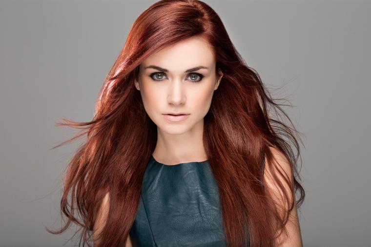Donna con i capelli lunghi di colore rosso, sfumature color rame che mettono in evidenza la scalatura