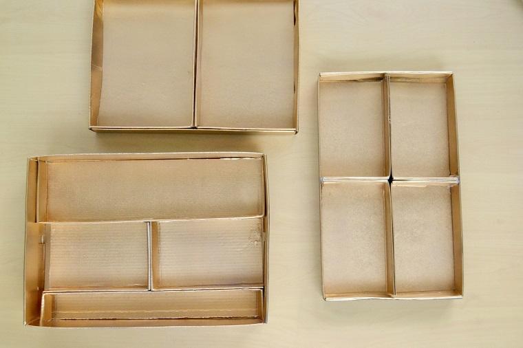 Riciclo creativo per un contenitore di cartone color oro con diversi scomparti