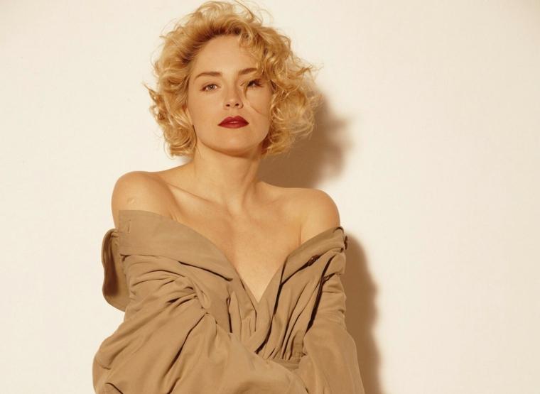 Acconciatura stile anni '50 con capelli biondi e ricci per Sharon Stone, camicia uomo colore beige