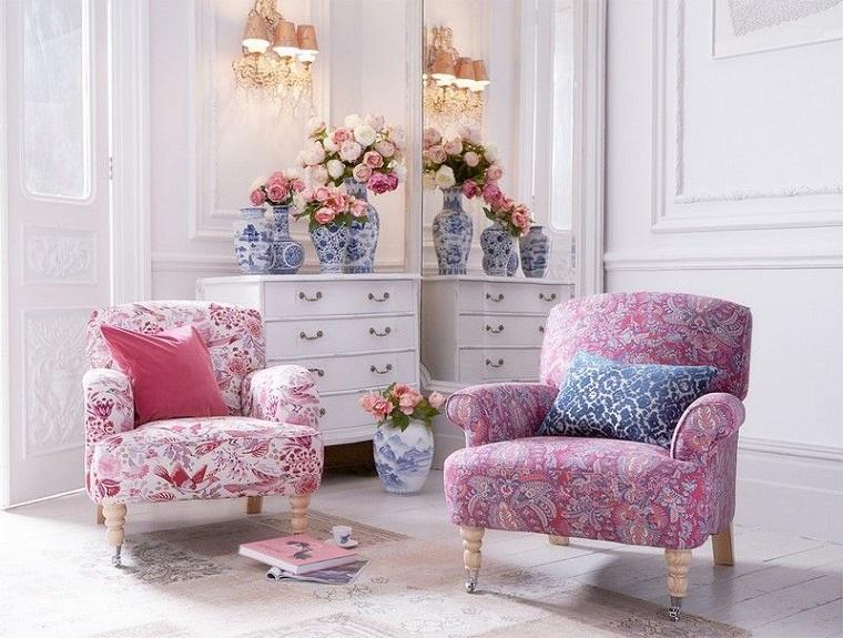 Mobili shabby chic con print floreali, poltrone e mobile in legno di colore bianco con vasi di fiori e uno grande specchio