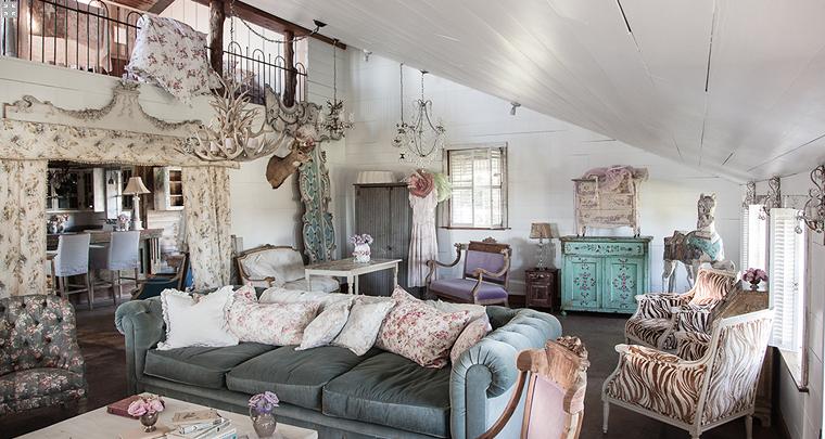 https://archzine.it/wp-content/uploads/2018/01/soggiorno-decorazioni-shabby-chic-mansarda-tende-motivi-floreali-soffitto-legno-divano-mobili-legno.png