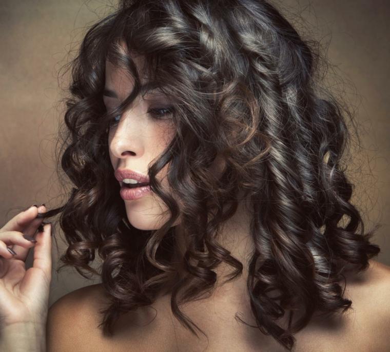 taglio capelli scalato, un'acconciatura a boccoli su capelli di media lunghezza castano scuri