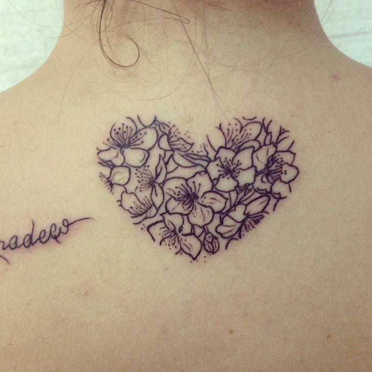 un tatuaggio sulla schiena a forma di cuore con all'interno dei fiori e una scritta a lato