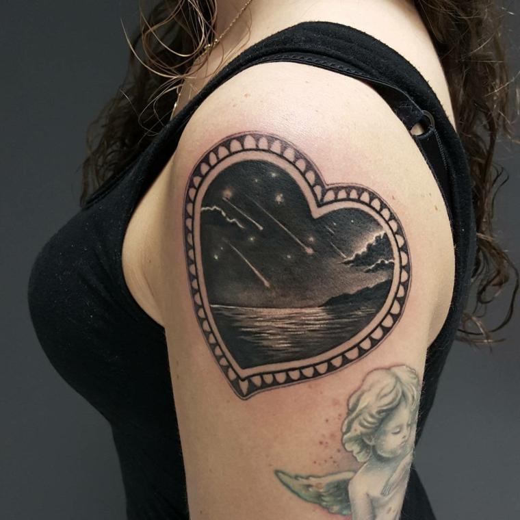 un braccio femminile con un tattoo cuoricino con disegnato all'interno un paesaggio notturno