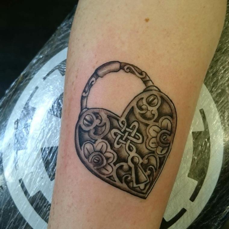 un tatuaggio a forma di lucchetto-cuore con delle decorazioni all'interno