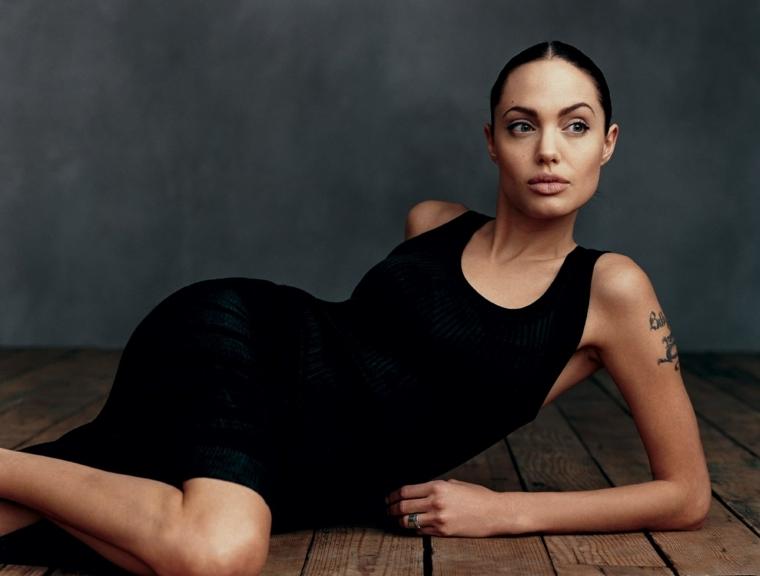 Angelina Jolie e attrici americane con tatuaggi sul braccio, vestito nero lungo casual