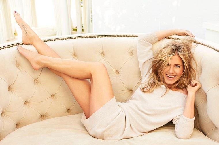 Jennifer Aniston vestita con un magione lungo e seduta su un divano classico beige
