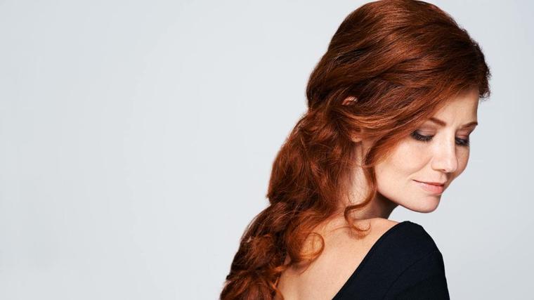 Donna con capelli lunghi di colore rosso con sfumature strawberry legati all'indietro