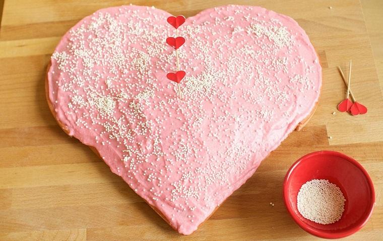 Idea per una torta a cuore con glassa rosa e decorazione con granelli di zucchero