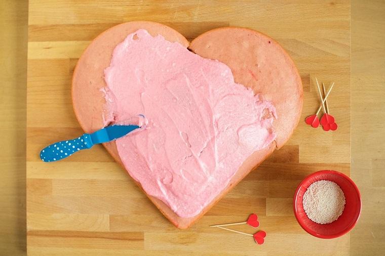 Decorare la torta con una glassa di colore rosa e decorare con granelli di zucchero