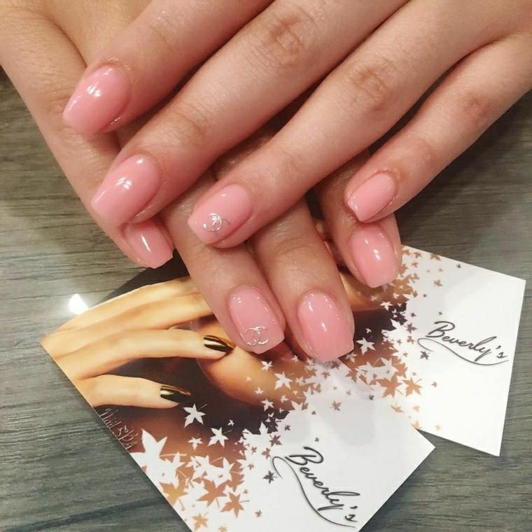 Decorare le unghie con il simbolo di Chanel di colore grigio su una base rosa luminosa