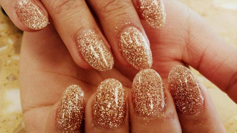 Decorazioni unghie con uno smalto glitter color miele, forma a mandorla di media lunghezza