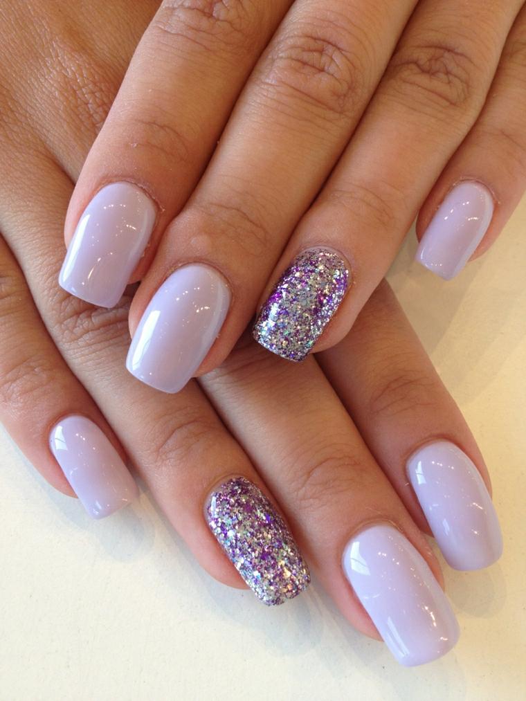 Smalto acrilico di colore viola molto chiaro e accent nail sul dito anulare glitter della stessa tonalità