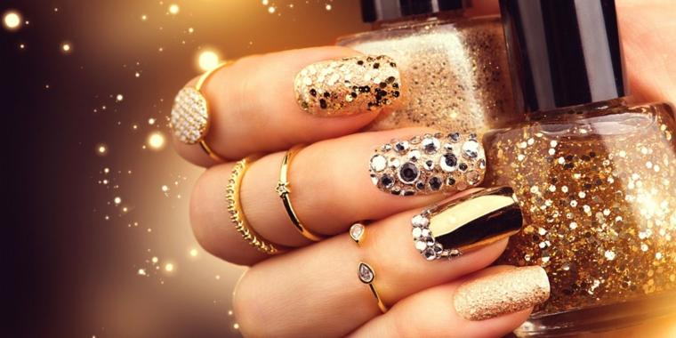 Decorazioni unghie lunghe con brillantini, glitter e smalto mat, tanti anelli in oro