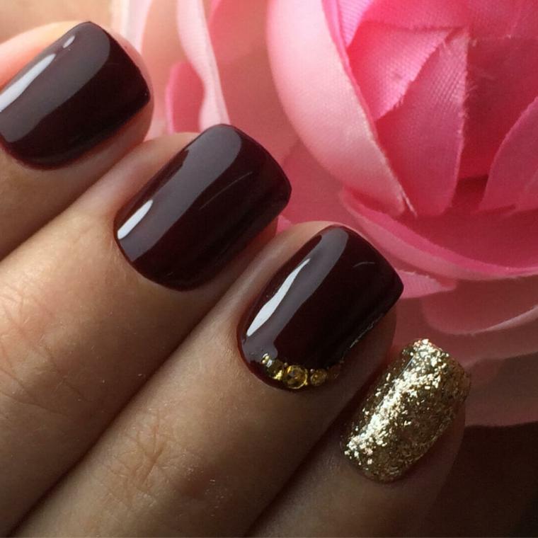 Decorazioni unghie di colore bordeaux con piccoli brillantini sul dito anulare e glitter sul mignolo