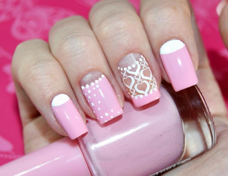 Decorazioni con puntini bianco su una base di smalto rosa, disegno cuori e french inversa