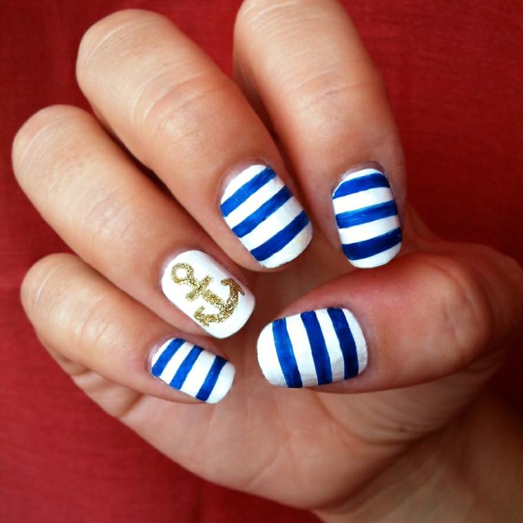 Unghie decorate in stile navy con ancora sul dito anulare, smalto base bianco con linee blu