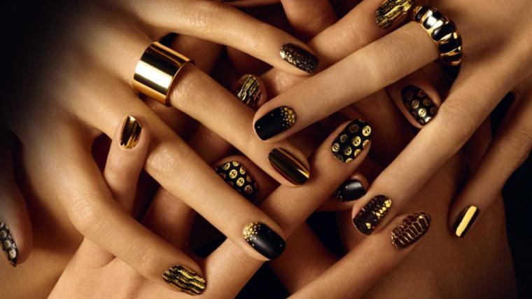 Decorazioni unghie di colore nero con print in oro, abbinamento agli anelli