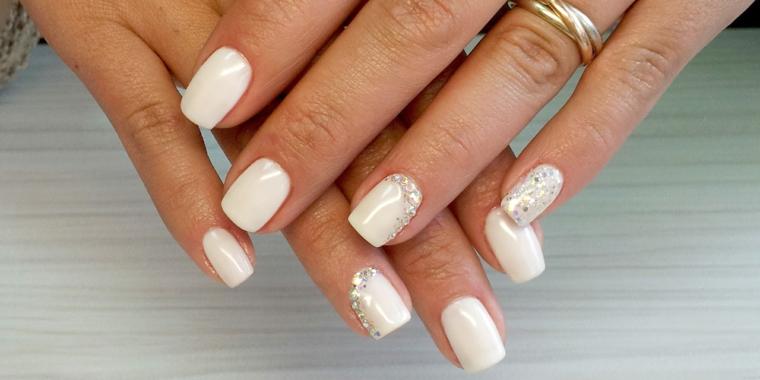 Decorazioni con brillantini per delle unghie di colore bianco dipinte con smalto gel