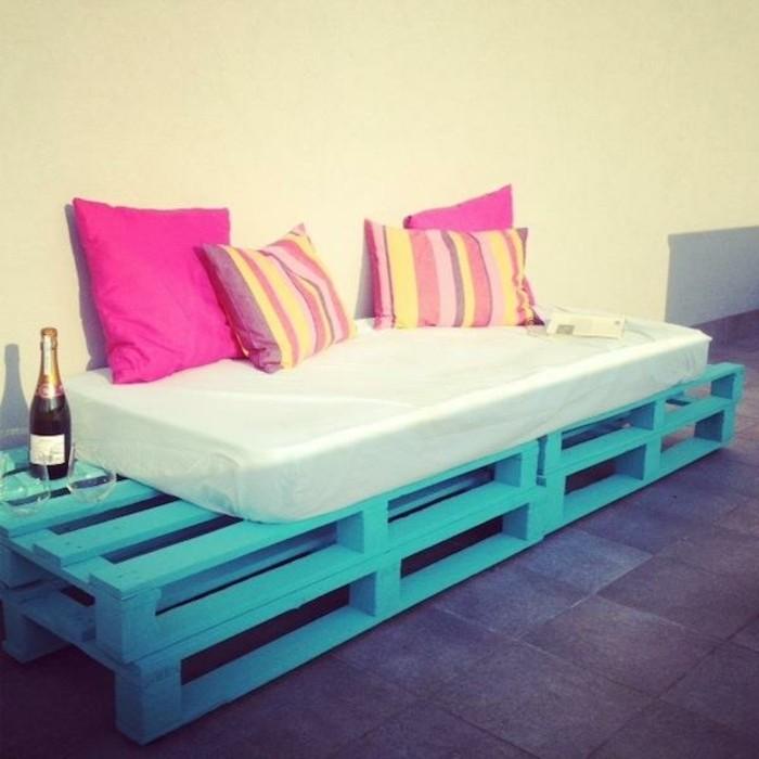 Arredamento terrazzo con divano bancali, dipinto colore blu, decorazioni con cuscini colorati