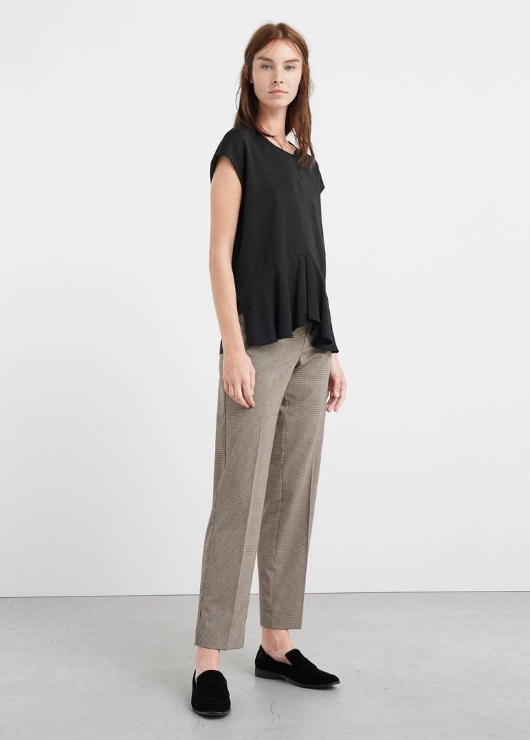 Maglietta nera in abbinamento ad un pantalone grigio, mocassini neri in velluto