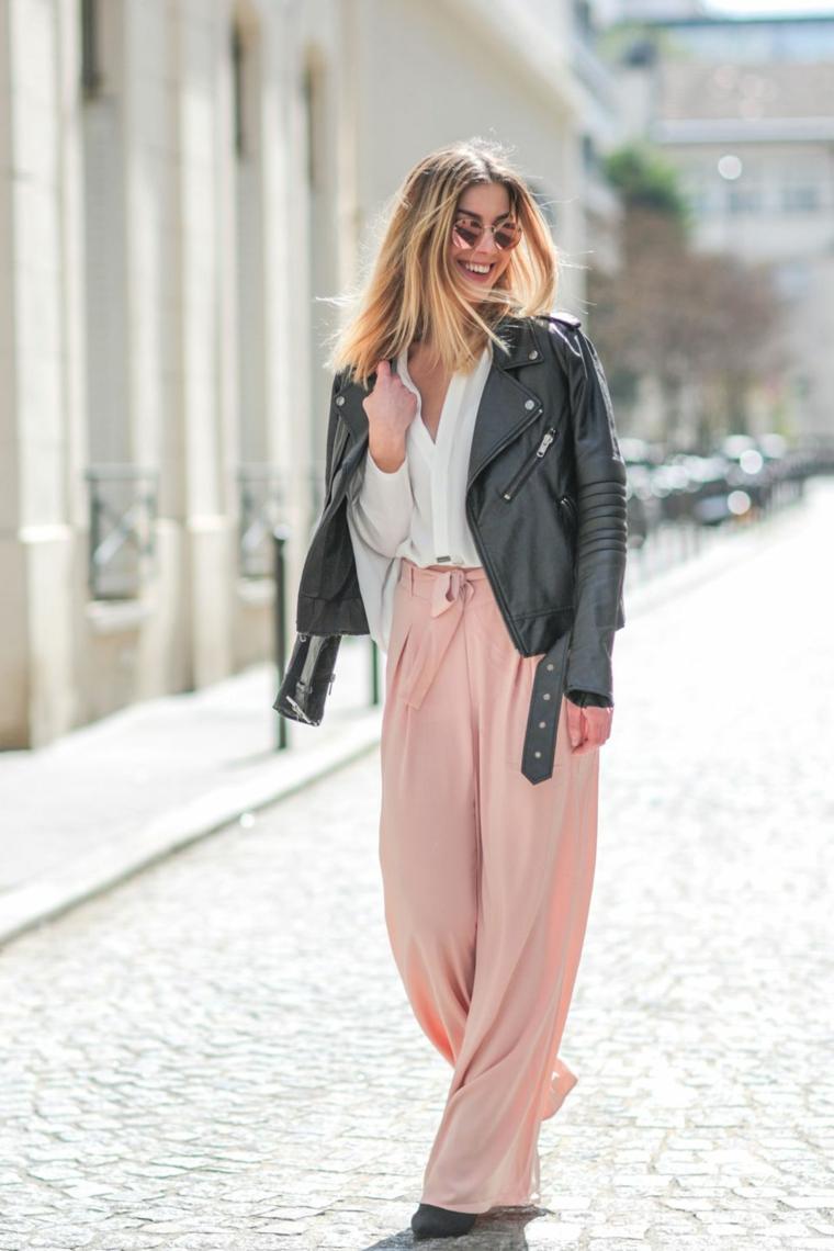 Pantalone rosa fluido in abbinamento ad una camicia bianca, giacca di pelle nera